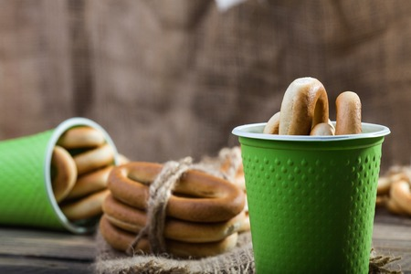 bind: Photo closeup groups of delicious hard oval cracknels bind with string in bunches in threes and in two disposable green cups laying on sackcloth over blurred rustic background, horizontal picture