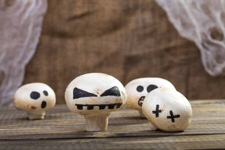 ghost face: Photo still life set of four Halloween white button mushrooms champignons with ghost face smiles drawn in black felt pen standing on wooden table over blurred rustic background, horizontal picture