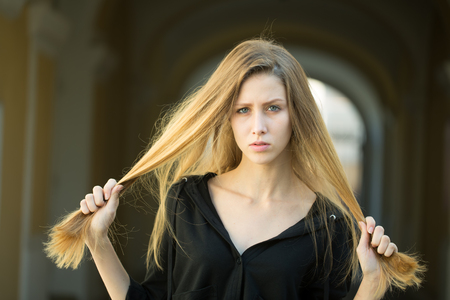 Closeup portrait of one beautiful serious cool blonde young woman with long hair outdoor looking forward on blurred background, horizontal picture