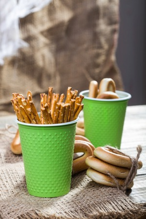 hard stuff: Still life two disposable green cups containing stick biscuits hard oval cracknels and bunches bind with string lying on sackcloth wooden table on rustic background, vertical picture Stock Photo