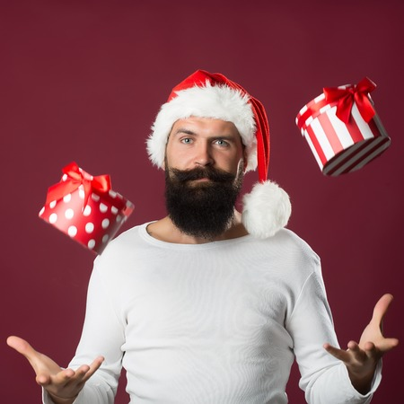 long beard: Portrait of one handsome new year man with long beard and moustache in red santa claus christmas hat with fur holding present box in air in studio on purple background, square picture Stock Photo