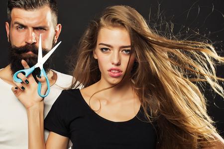 tijeras: Vista de detalle de la joven y bella pareja de la bella corte del peluquero de moda femenina y tijeras que sostienen y hombre guapo con barba larga en estudio en fondo negro, cuadro horizontal