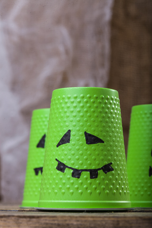ghost face: Photo still life closeup one disposable green cup with Halloween ghost face drawn in black felt pen on wooden table on blurred group of disposable tableware background, vertical picture Stock Photo