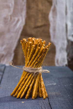 string together: Photo of bread and flour products one sheaf of delicious stick biscuits straws tied together with string standing on blue wooden table on blurred rustic background, vertical picture