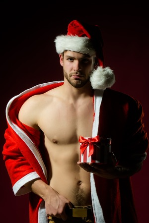 Closeup portrait of one handsome sexy new year young muscular man with bare chest in red christmas santa claus winter coat with hood holding present box on pink studio background, vertical picture Stock Photo