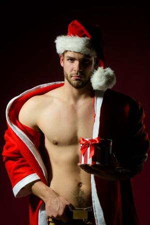 beau jeune homme: portrait Gros plan d'une nouvelle ann�e beau jeune homme sexy musculaire avec la poitrine nue de no�l p�re no�l manteau rouge d'hiver avec capuche tenant pr�sent encadr� sur fond rose studio, image verticale