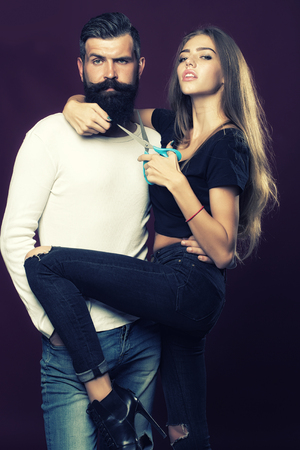 long beard: One young beautiful couple of beautiful female barber holding scissors and handsome man with long beard standing in studio on purple background, vertical picture