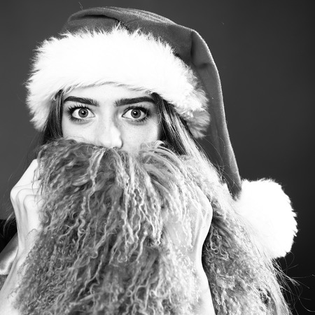 long beard: Closeup portrait of one beautiful young surprised new year woman in santa claus christmas hat with fur and waistcoat as long beard in studio black and white, square picture Stock Photo