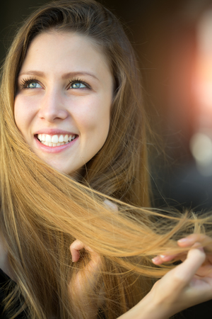 sidewards: Closeup portrait of one beautiful happy smiling blonde young woman with long hair outdoor looking away on blurred background, vertical picture Stock Photo