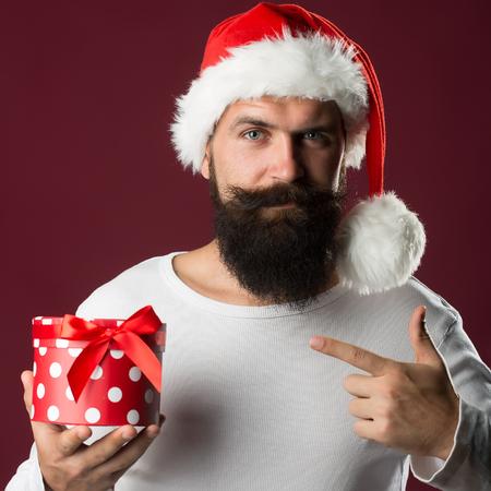 Portrait of one handsome new year man with long beard and moustache in red santa claus christmas hat with fur holding and showing on present box in studio on purple background, square picture