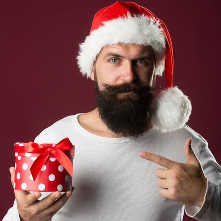 hombre rojo: Retrato de un nuevo hombre guapo años con una larga barba y bigote en rojo sombrero de santa claus con tenencia de pieles y que muestra en el cuadro actual en el estudio sobre fondo morado, imagen cuadrada Foto de archivo