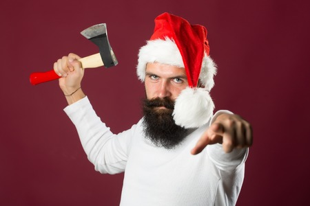 long beard: Portrait of one handsome new year man with long beard and moustache in red santa claus christmas hat with fur holding sharp axe in studio on purple background, horizontal picture