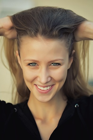 sidewards: Portrait closeup of pretty blond girl joyful smiling face with blue eyes straight long hair pinning hands to head posing in black outdoors on grey background, vertical picture Stock Photo