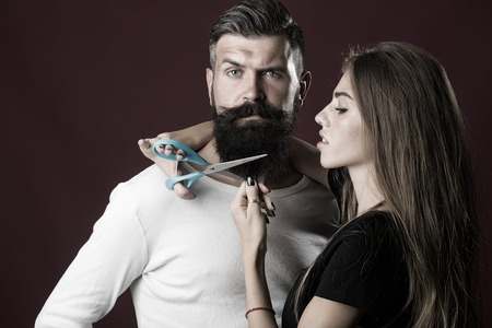 long beard: Closeup view of young beautiful couple of beautiful female barber cutting with scissors long beard of handsome man in studio on purple background, horizontal picture Stock Photo