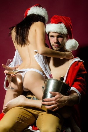 Young sexual new year couple of woman in corset and red christmas hat embracing muscular man in santa claus winter coat holding wine bottle with cork in pail in studio on purple background, vertical Stock Photo