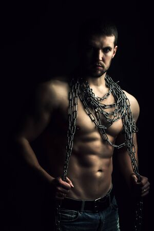 One handsome sexual strong young man with muscular body in blue jeans holding rope with hands hanging on neck and shoulders standing posing in studio on black background, vertical picture Фото со стока