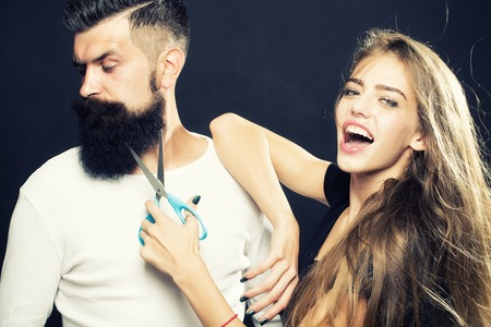long beard: Closeup view of young beautiful couple of beautiful fashionable female barber cutting and holding scissors and handsome man with long beard in studio on black background, horizontal picture