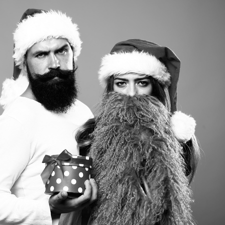 long beard: Young beautiful happy new year couple of man with long beard with present box and woman in red santa christmas hat with fur in studio black and white, square picture