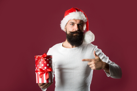 sexual background: Portrait of one handsome new year man with long beard and moustache in red santa claus christmas hat with fur holding present box in studio on purple background, horizontal picture