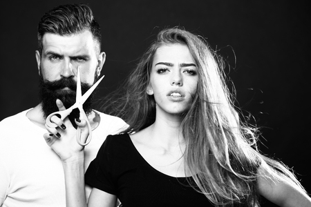 Closeup view of young beautiful couple of beautiful fashionable female barber cutting and holding scissors and handsome man with long beard in studio black and white, horizontal picture
