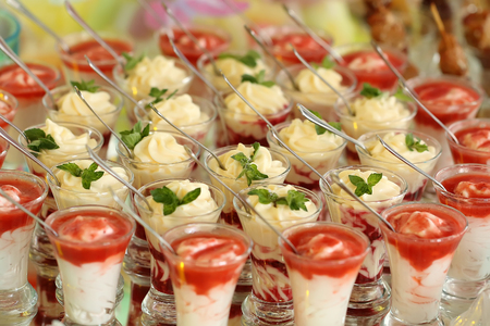 decadent: Photo closeup plenty lots of small decadent creamy layer desserts red and white in glasses with tea-spoons decorated with mint on seamless blurred background, horizontal picture