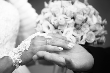 matrimony: Photo closeup of newlyweds groom holding hand of bride with wedding rings rites of matrimony black and white on bridal bouquet background, horizontal picture Stock Photo