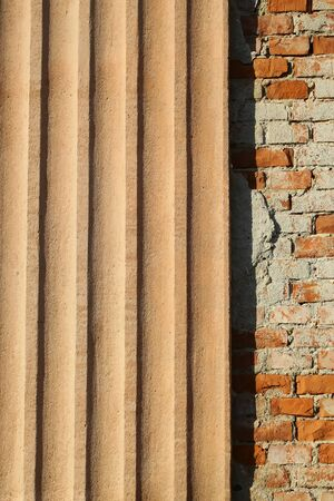 sandy brown: Photo closeup outdoor wall made of warm plastered terracotta colored ribbed finish plate panel and  brown sandy bricks facade exterior on mural background, vertical picture