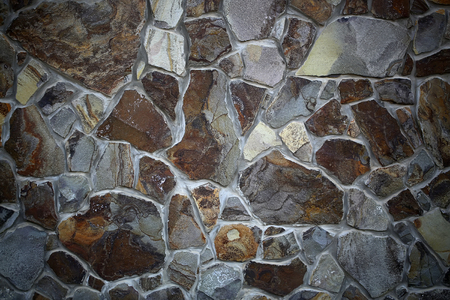 concrete blocks: Photo closeup outdoor of brown gray stone wall facade exterior of rocks of various sizes and forms on seamless mural background, horizontal picture Stock Photo