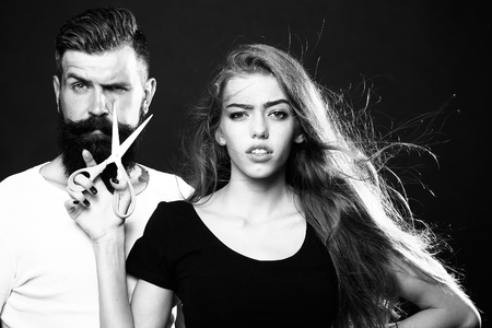 long beard: Closeup view of young beautiful couple of beautiful fashionable female barber cutting and holding scissors and handsome man with long beard in studio black and white, horizontal picture