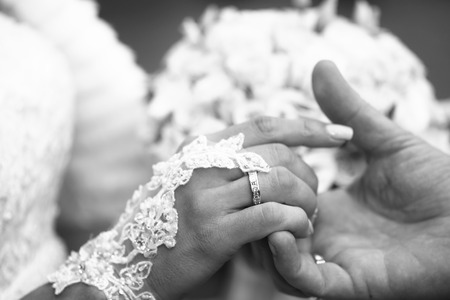 Photo closeup of newlyweds groom holding hand of bride with wedding rings rites of matrimony black and white on blurred bridal bouquet background, horizontal picture Stock Photo