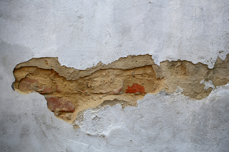 flaked: Photo closeup of shabby damaged red brick wall with peeled old chipped flaked gray plaster cover outdoor on concrete mural background, horizontal picture
