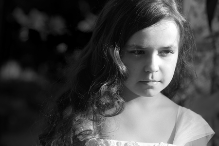 frizzy: Closeup portrait of pretty serious pensive little girl with loose frizzy hair and long eyelashes in dress outdoor, black and white horizontal photo Stock Photo