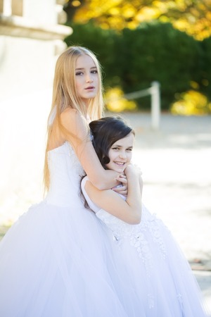 frizzy: Lovely blond teenage with long hair huges cute smiling little girl with frizzy dark hair in white beautiful fluffy dresses outdoor, vertical photo