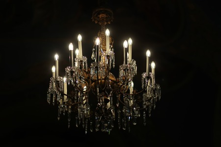 cutglass: Photo closeup one classic crystal cut-glass grand chandelier lighting fixture ceiling lamp with electric opal bulbs pendants switched on illuminating darkness over black background, horizontal picture