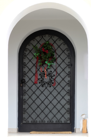 plastered wall: Photo closeup of decorated old arched closed front door with black metal bars with holiday wreath and mat over white beige plastered wall background, vertical picture Stock Photo