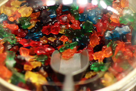 sweeties: Photo closeup selection of variety mixed colorful gummy jelly bears gumdrops candies sweeties in plastic bowl with scoop for pick and sale on gum confectionery background, horizontal picture
