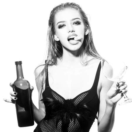 breast beauty: One pretty young sexy woman in black underwear with long wet hair holding wine bottle glass and cork in mouth standing in studio on white background, square picture