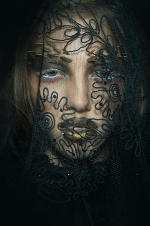 black makeup: Closeup view portrait of one attractive sensual wild young woman with bright golden animal makeup with thorns on face in lace veil in studio on black background, vertical picture