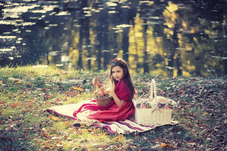 grassplot: Pretty little girl in red dress shawl and flower wreath on frizzy dark hair holding small fruit basket near big white basket with pumpkin on striped rug on shore lake in autumn, horizontal photo