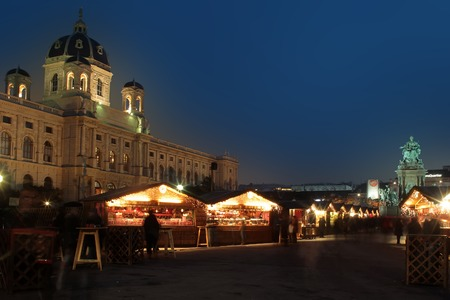 holiday lighting: Photo of snowless evening Christmas market square with wooden stalls with holiday decorative illumination lighting in city centre streetscape over dark blue sky background, horizontal picture