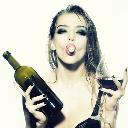 One pretty young sexy woman in black underwear with long wet hair holding wine bottle glass and cork in mouth standing in studio on white background, square picture