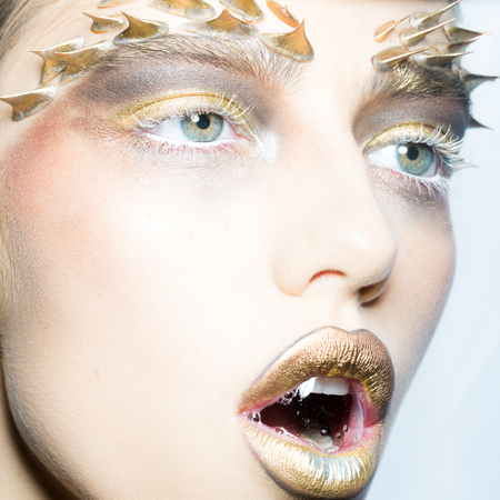 animal woman: Closeup portrait of one beautiful sexy wild young woman with bright golden animal makeup with thorns on face with bubble in open mouth in studio on white background, square picture