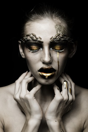 animal eye: Closeup portrait of one beautiful sexy wild young woman with bright golden animal makeup with thorns on face in studio on black background, vertical picture