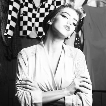 正方形の多く明るい服黒と白の間でワードローブの頭に立ってのローラの髪のガウンで一人の美しい若い物思いにふける性的主婦女性の拡大画像