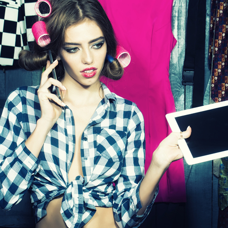 haircurlers: One beautiful sexy young stylish woman in checkered shirt with hair-rollers on head with laptop and mobile phone standing in wardrobe among many bright clothes, square picture