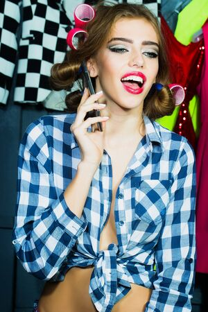 haircurlers: One smiling sexy young stylish woman in checkered shirt with hair-rollers on head with mobile phone standing in wardrobe among many bright clothes, vertical picture Stock Photo