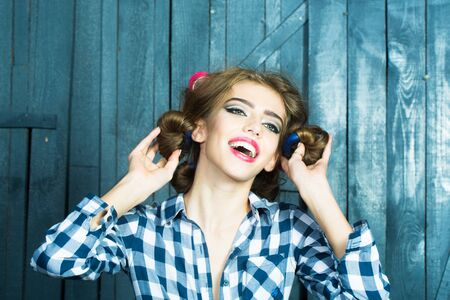 haircurlers: One beautiful sexy young stylish woman in checkered shirt and skirt with hair-rollers on head standing indoor on wooden wall stuio background, horizontal picture