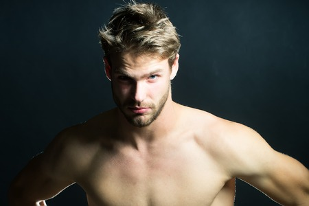 boy  naked: Closeup view portrait of one handsome young muscular naked sexy macho man with short hair bare chest abd beautiful body standing in studio on black backdrop, horizontal picture