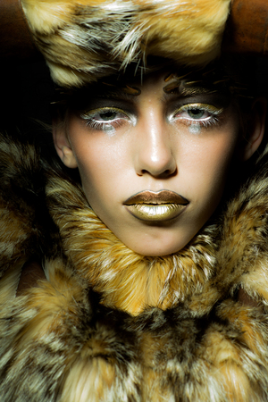 black makeup: Closeup portrait of one beautiful wild young woman with bright golden animal monkey makeup with thorns on face in fur coat in studio, vertical picture Stock Photo
