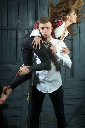 modelos posando: hermosa joven pareja de hombre de camisa blanca que sostiene la mujer bastante delgada con el pelo largo en la blusa a cuadros y pantalones vaqueros de pie en el estudio sobre fondo de madera, imagen vertical
